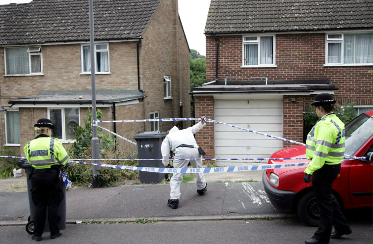 Police officers stand guard outside on Saturday as a forensic officer enters the houseof one of the arrested suspects in High Wycombe, England.