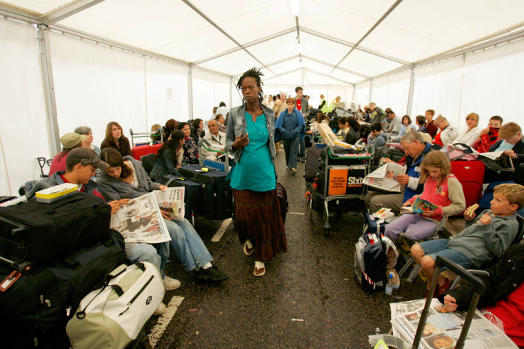 Passengers needing to check in for flights wait in a tent errected outside of Lodon's Heathrow Airport's terminal four on Monday.