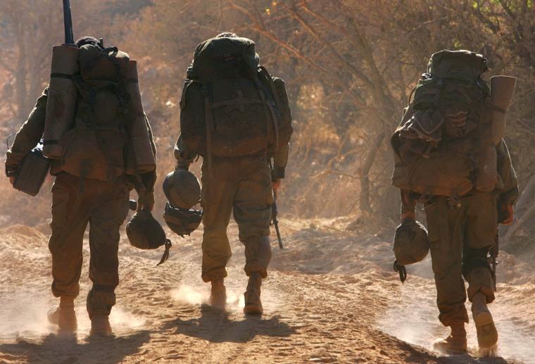 Israeli soldiers cross the border between Lebanon and Israel near the border village of Malkiya on Tuesday.