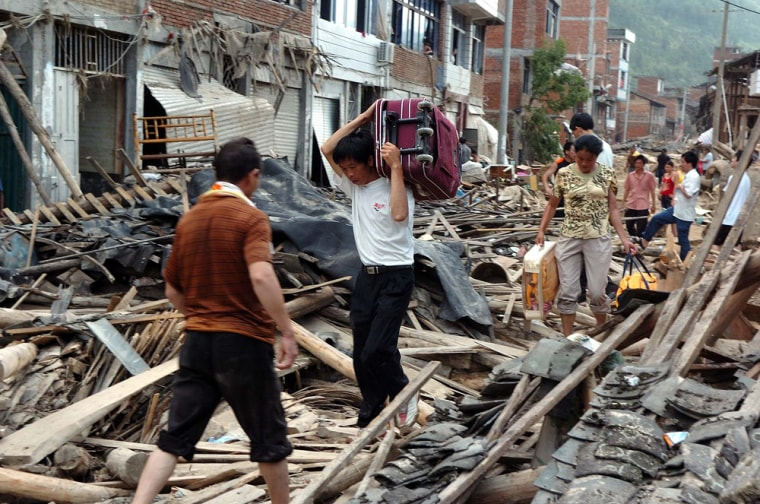 Residents recover belongings among the ruins of their houses in Tuoxi, in southeast China's Fujian Province,on Monday.