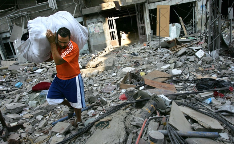 A man carries belongings salvaged from his destroyed apartment building after returning to his home in the southern suburbs of Beirut, on Wednesday.
