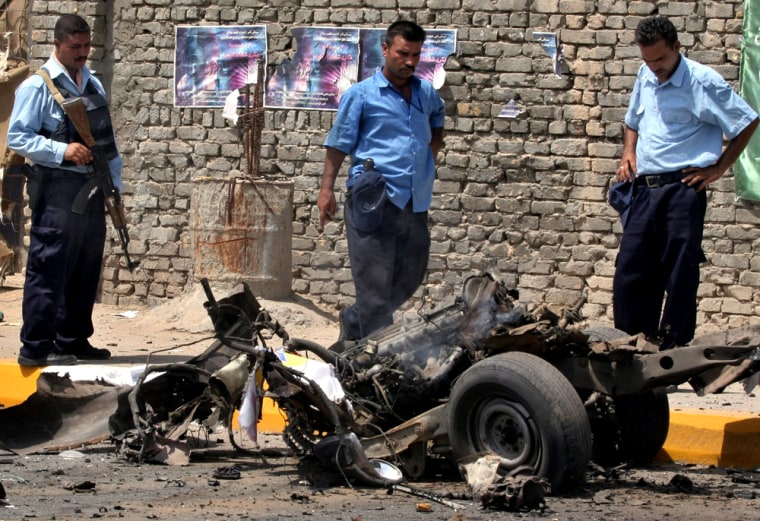 Policeman survey the scene of a car bomb attack in Mansour district in west-central Baghdad