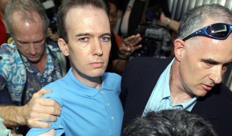 Unidentified U.S. officials escort US teacher John Mark Karr at the Thai Immigration Department in Bangkok, August 17, 2006.