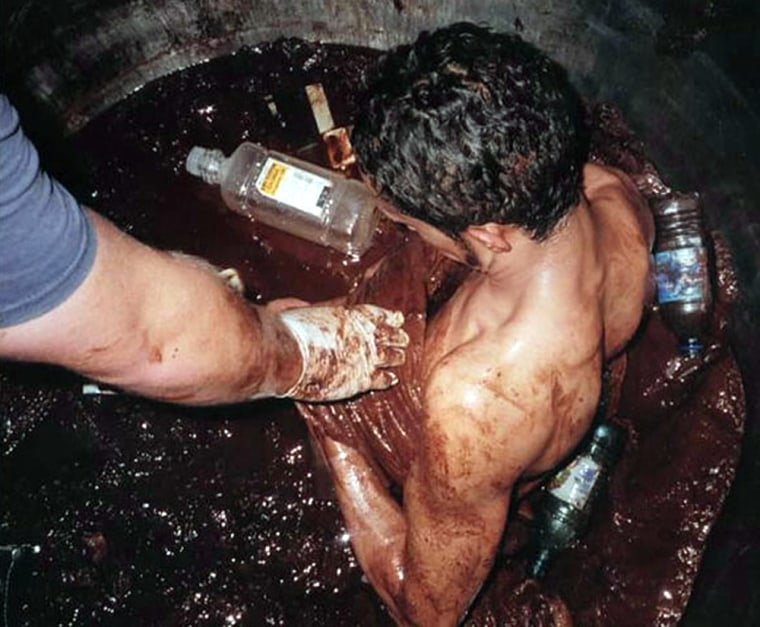 Rescue workers attempt to free Darmin Garcia from the vat of chocolate Friday morning.