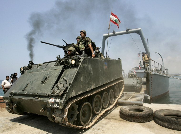 Lebanese soldiers who will be deployed to the south of the country drive an armored vehicleout of a navy ship at the port in Tyre on Thursday.