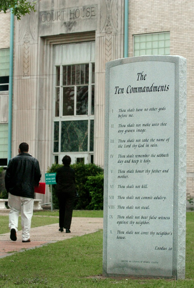 People walk past a monument of the Ten Commandments located on the grounds of the Haskell County courthouse in Stigler, Okla., in an April 2006 file photo.