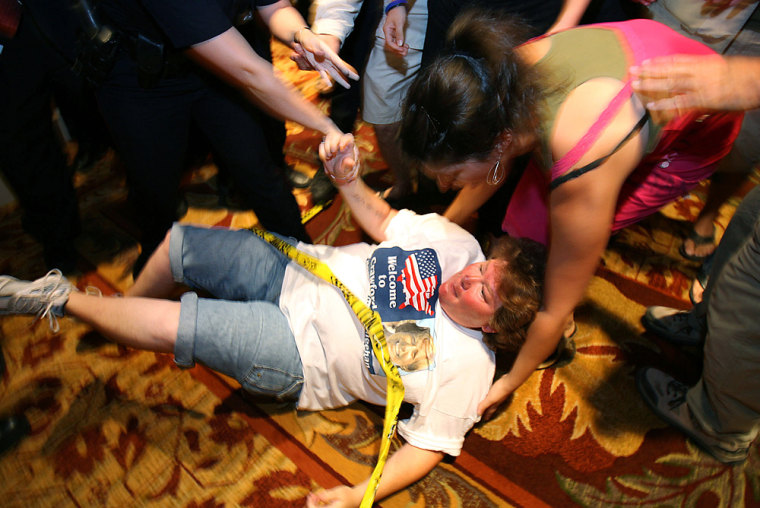 A demonstratorfalls tothe ground during Saturday night's scuffle.