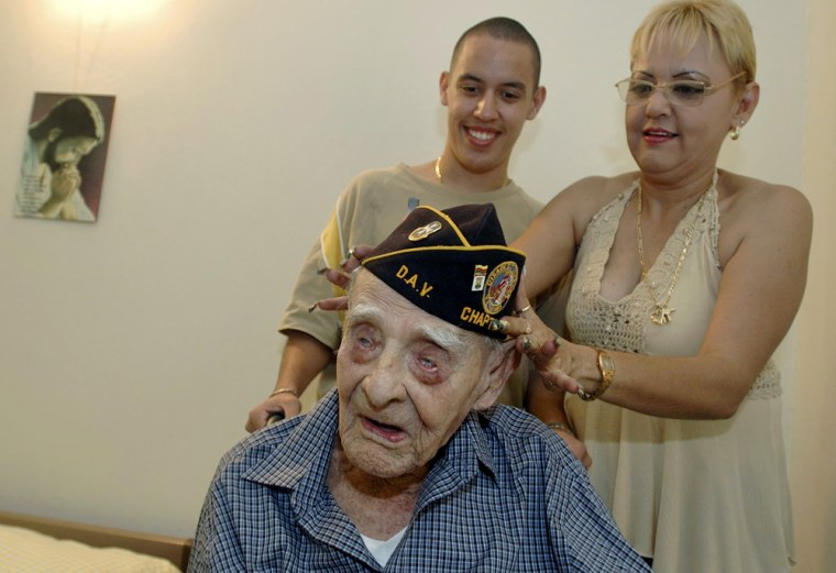Emiliano Mercado del Toro sits Monday as his great niece, Dolores Martinez, helps put on his old U.S. Army veteran cap, and her son Arturo looks on, at Del Toro's home in Isabela, P.R.