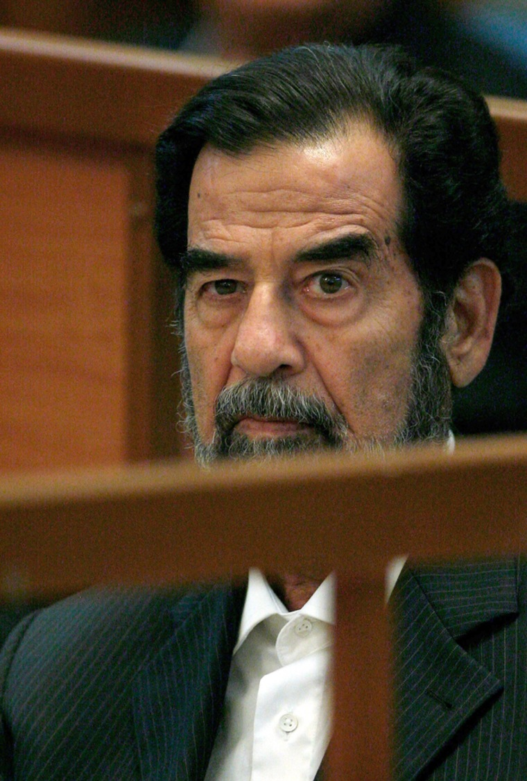 Former Iraqi leader Saddam Hussein looks on during the first day of his trial in Baghdad