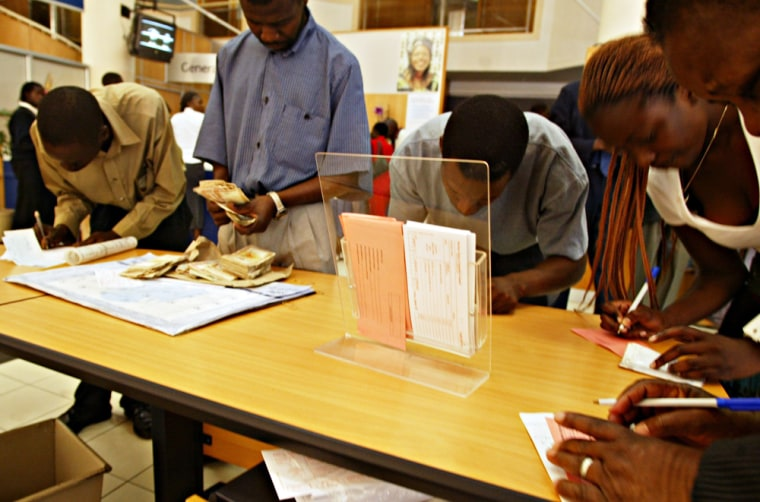 Unidentified Zimbabweans fill in deposit slips to exchange old currencyfor new inside a local bank in Harare on Monday.