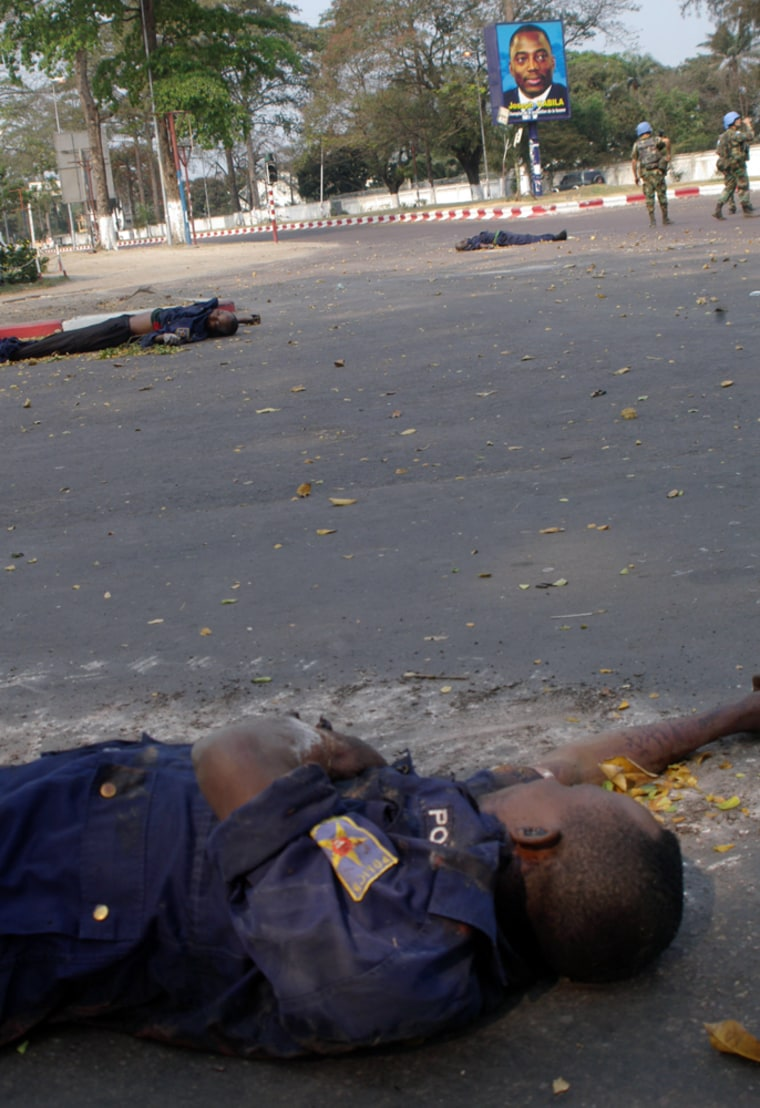 Congo police officers lie dead Tuesday as U.N. troops patrol in the background in Kinshasa, Congo. TheU.N. called for an immediate cease-fire between rival army supporters of Congo's two presidential candidates.