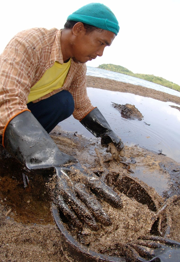 Villager collects oil waste at Tandok village in Guimaras island in central Philippines