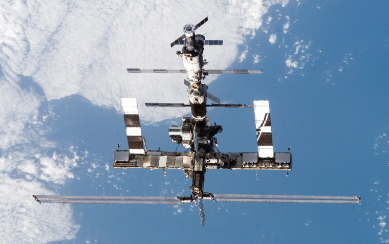 Backdropped by a blue and white Earth, the international space station moves away from the space shuttle Discovery in July.
