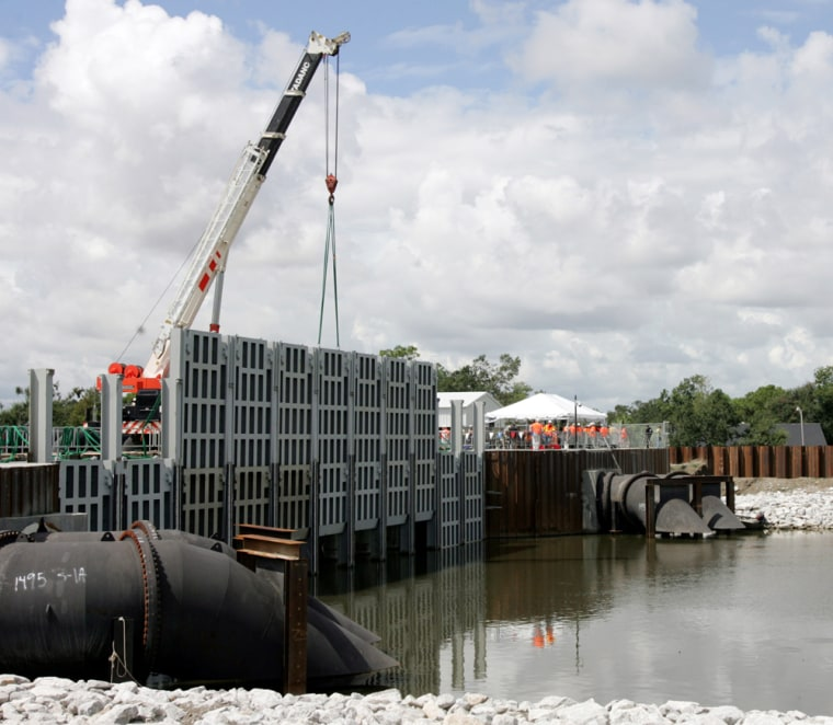 Sections of new flood gates are lowered into the London Ave. Canal during a demonstration in New Orleans on Saturday. Levees along the canal failed during Hurricane Katrina.