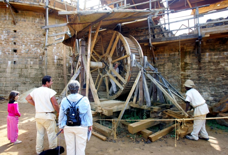 Tourists watch workers man a wooden spinning wheel, activating a pulley system to lift a load of stones atop a tower, at the Guedelon castle construction site, in a forest in Burgundy, 125 miles south of Paris, Aug. 1.
