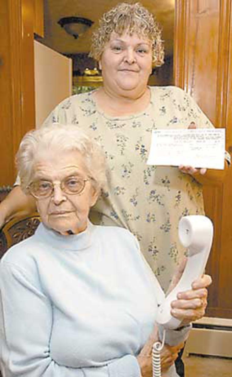 Cinda Howell stands behind her mother, Ester Strogen, holding a phone bill. Howell and other family members were upset when they found out Ester Strogen had been leasing rotary dial telephones for the past 42 years from AT&T.