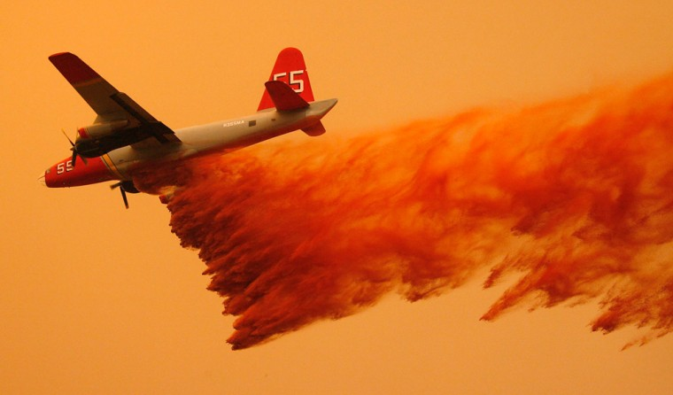 A California Department of Forestry air tanker drops fire retardant Sundayon the large fire burning near Ojai, Calif.