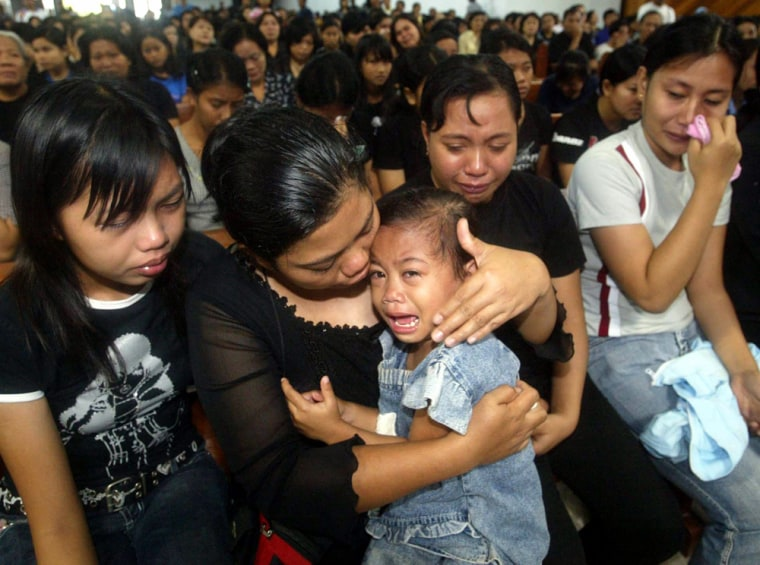 Relatives mourn during a memorial service in Santa Maria Church in Palu