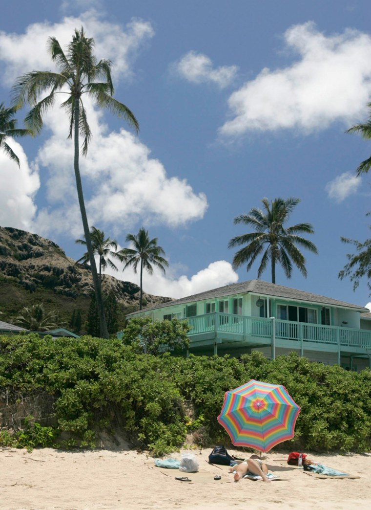 A sunbather lounges on Lanikai Beach in front of million dollar-view homes, in Lanikai, Hawaii.