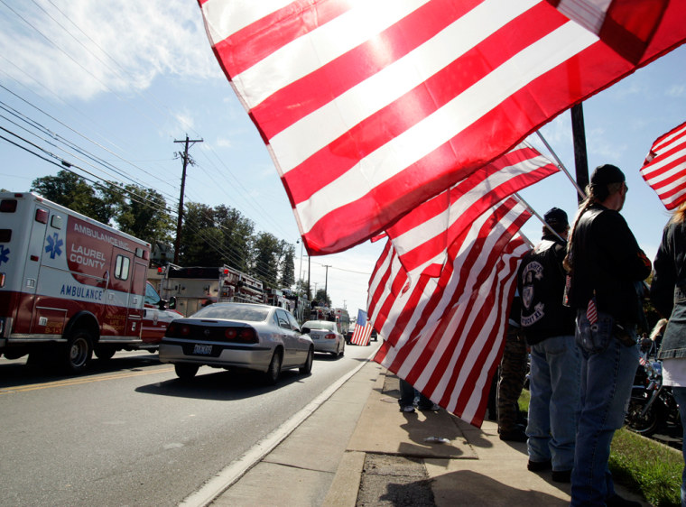 Rob Duff, of Corbin, Ky. far right, holds an American flag in front of the London Funeral Home where services were being held for Sgt. 1st Class Charles Jason Jones in London, Ky., on Saturday.