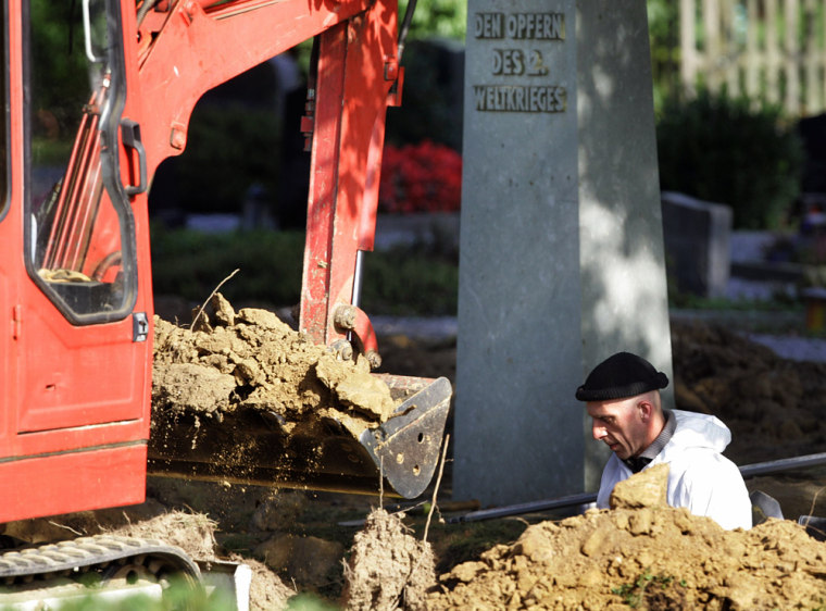 Workers examine a mass grave on the churchyard in Menden