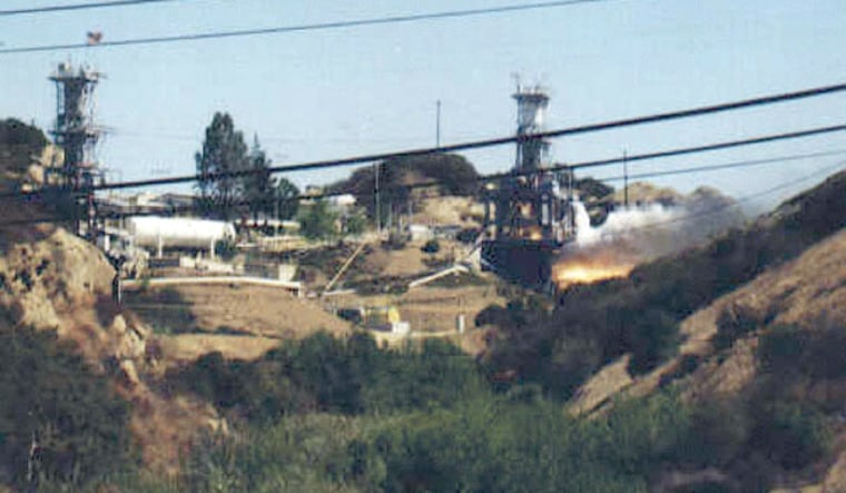 Smoke from a rocket test at the Santa Susana Field Laboratory is seen at right. The lab has been studied for years because of fears of chemical spills into the groundwater.