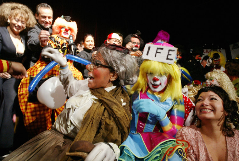 Clowns and guests burst balloons to kick off the Latin American Clown Convention at the Venustiano Carranza theatre on Monday in Mexico City.
