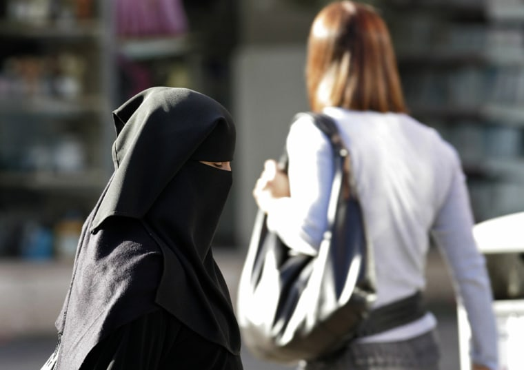 A Muslim woman wearing a veil walks along a road in the town in Blackburn, northern England