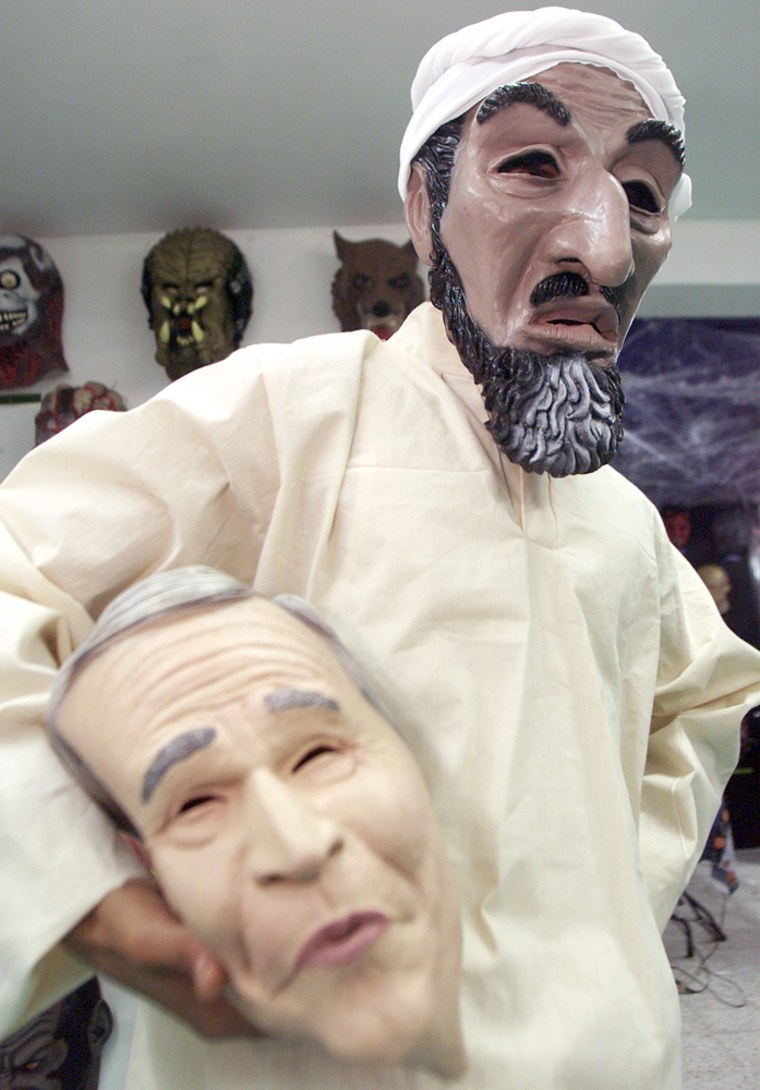 MEXICAN STORE WORKER SHOWS OFF BIN LADEN OUTFIT AND BUSH MASK.