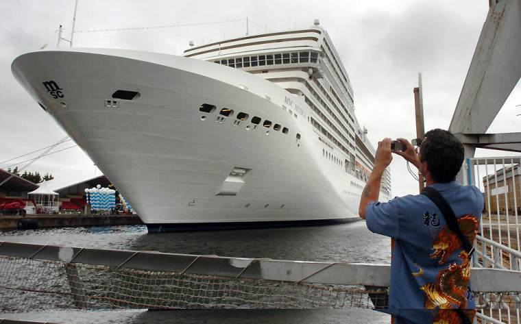A man takes a picture of the cruise ship