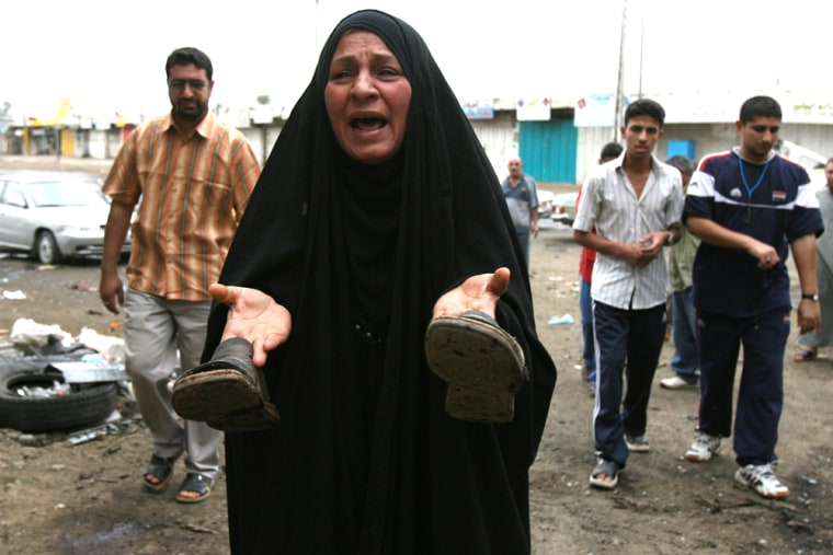 An Iraqi woman holds up the shoes of a relative who was killed in a car bomb blast that targeted a police patrol in central Baghdad on Monday. Three people died and 10 were wounded in the blast.