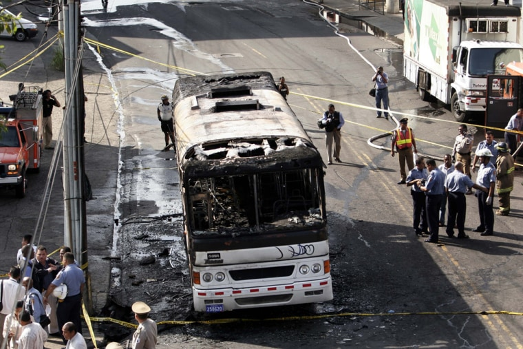 Police, firefighters and rescue workers stand Monday by a burned bus in Panama City, Panama. An official said the bus was operating with faulty brakes and no license plates.