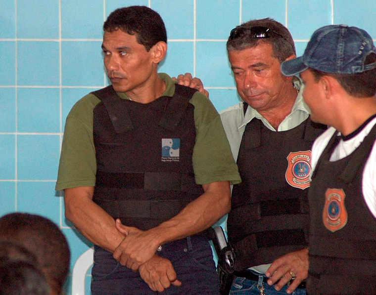 Francisco das Chagas Rodrigues de Brito, left, is escorted by police during his trial in Belem, Brazil, on Monday.