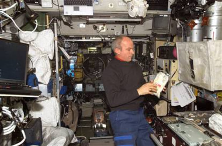 NASA astronaut Jeff Williams checks out a food pouch in the international space station's galley. Meals cooked up by chef Alain Ducasse were on board a cargo ship that blasted off Monday for the space station.