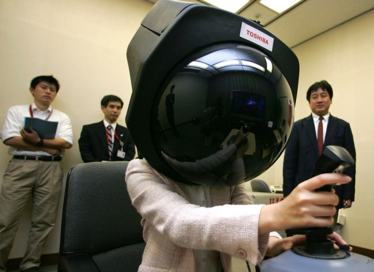 Toshiba Corp. employee Aira Hotta demonstrates prototype headgear that enables her to get a 360-degree view on a dome-shaped screen. Toshiba, which plans to market the gadget within 2 to 3 years, aiming at attracting people such as virtual reality gamers.