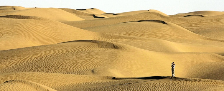 A visitor stands on sand dune in the Taklimakan Desert in northwest China's Xinjiang Uygur Autonomous Region, Wednesday, Oct. 11, 2006. The Taklimakan desert is one of the world's largest shifting sand deserts. (AP Photo/Eugene Hoshiko)