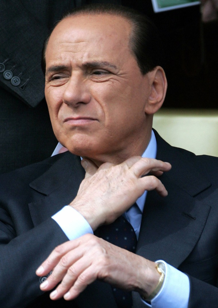 File photo of Italy's former PM Berlusconi adjusting his tie while watching a military parade in Rome