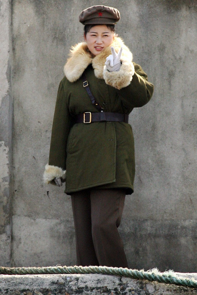 North Korean soldier gestures as she is being photographed, on the bank of the Yalu River near the North Korean town of Sinuiju, opposite the Chinese border town of Dandong