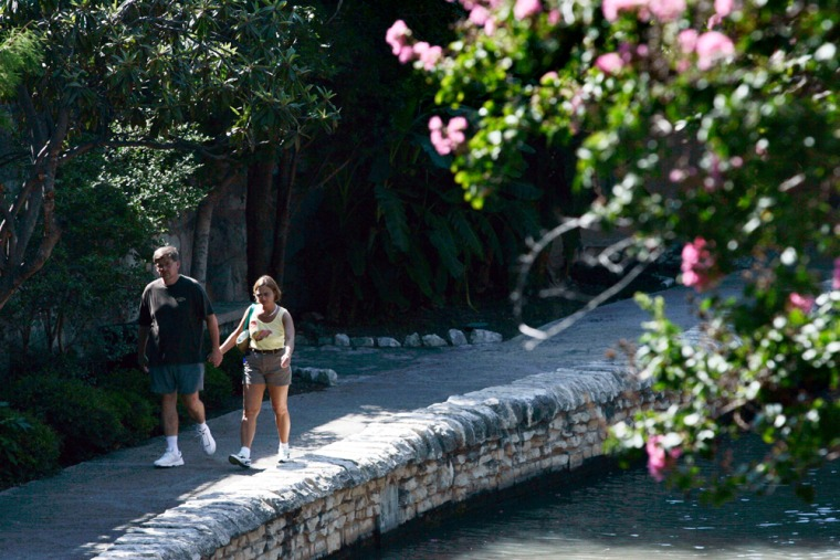 Joe Wilkos, left, and his wife Margaret stroll in a quiet section of the San Antonio, Riverwalk, Thursday, June 22nd, in San Antonio.
