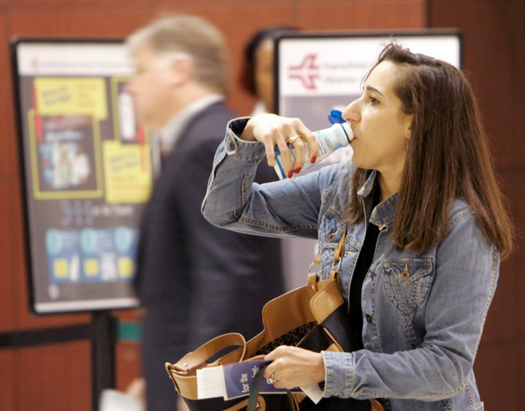 Jessica Pardi quickly downs a liquid beverage before entering the security check area at Hartsfield Jackson Atlanta International Airport in Atlanta on Thursday.