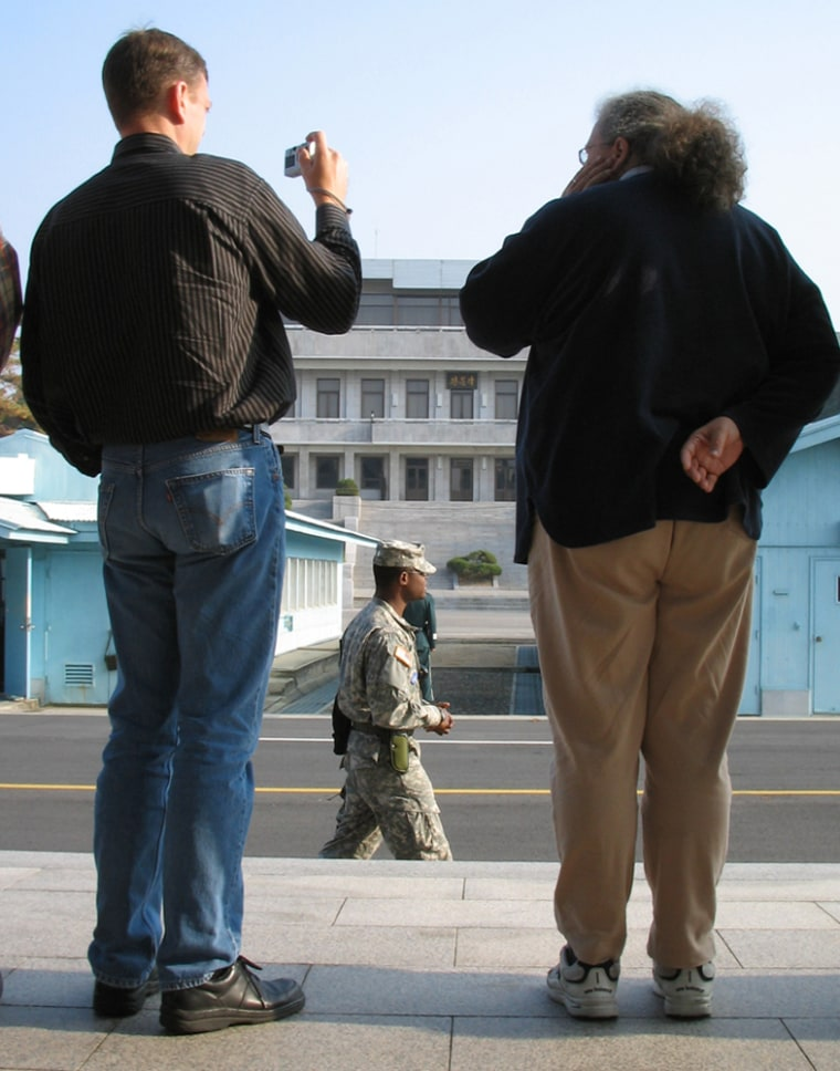 U.S. Sgt Nickenson Midi, 24, of Miami, Fla., center, walks past while tourists take pictures at the truce village of Panmunjom in the demilitarized zone (DMZ) that separates the two Koreas since the Korean War, north of Seoul earlier this month.
