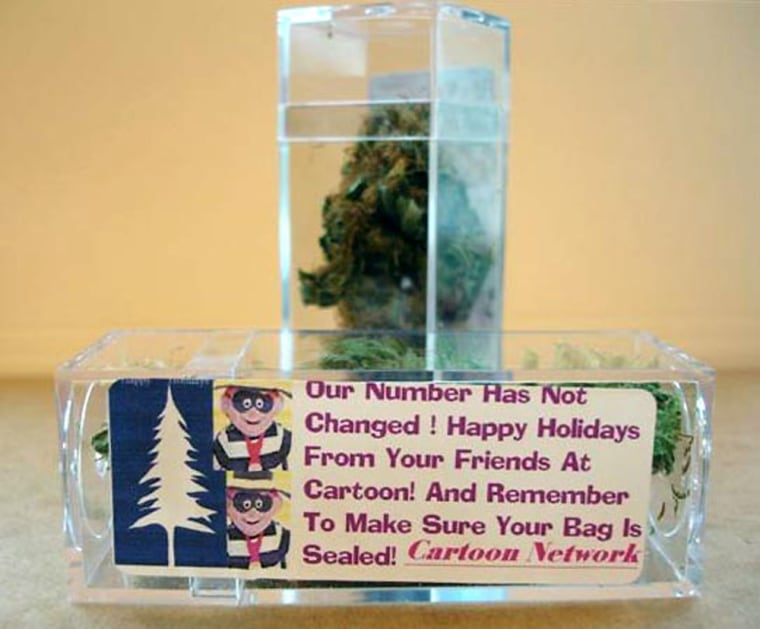 This photo supplied by Drug Enforcement Administration shows plastic boxes full of marijuana with an attached greeting from the Cartoon Network.