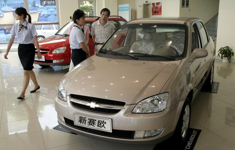 A clerk, center, shows a visitor aChevyat Yongda Auto in Shanghai, China. GM needs China — the world's third-biggest car market behind Japan and the U.S. — to provide growth it is unlikely to find here at home.