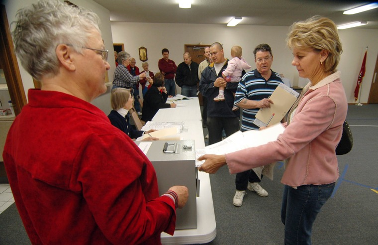 Sandy Kirkeycasts her ballot as a long line of people wait to vote on Tuesday at the Bethel Baptist Church in Brookings, S.D. A ballot measure that would ban nearly all abortions in the state drew money, volunteers and attention from national groups on both sides of the issue.