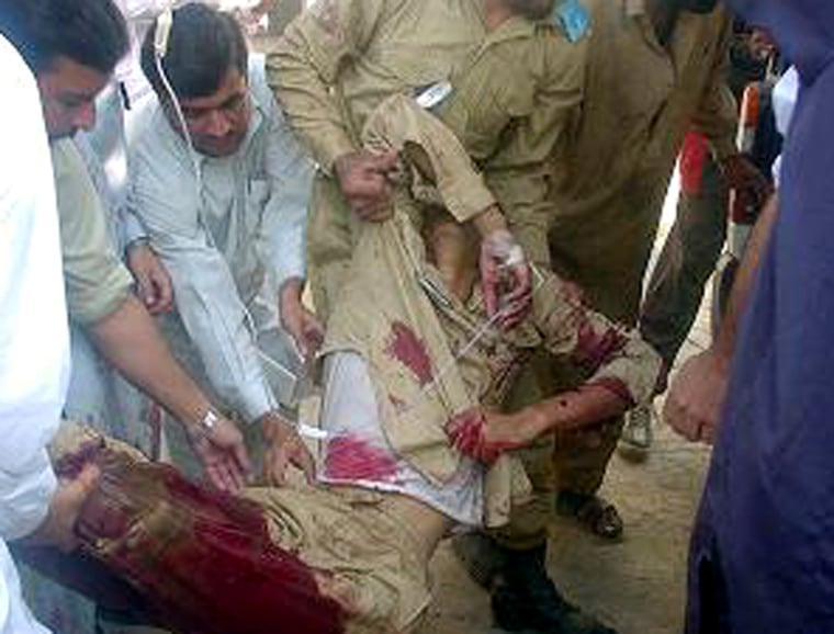 People carry an injured soldier after a suicide attack on an army training ground in Dargai