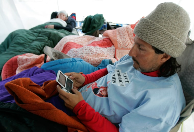 Al Jiminez, a senior at Gallaudet University, uses a wireless handheld computer to communicate with otherstudentactivists.Jiminez was participating in a hunger strike as students fought with school officials over their choice for the president of the university.