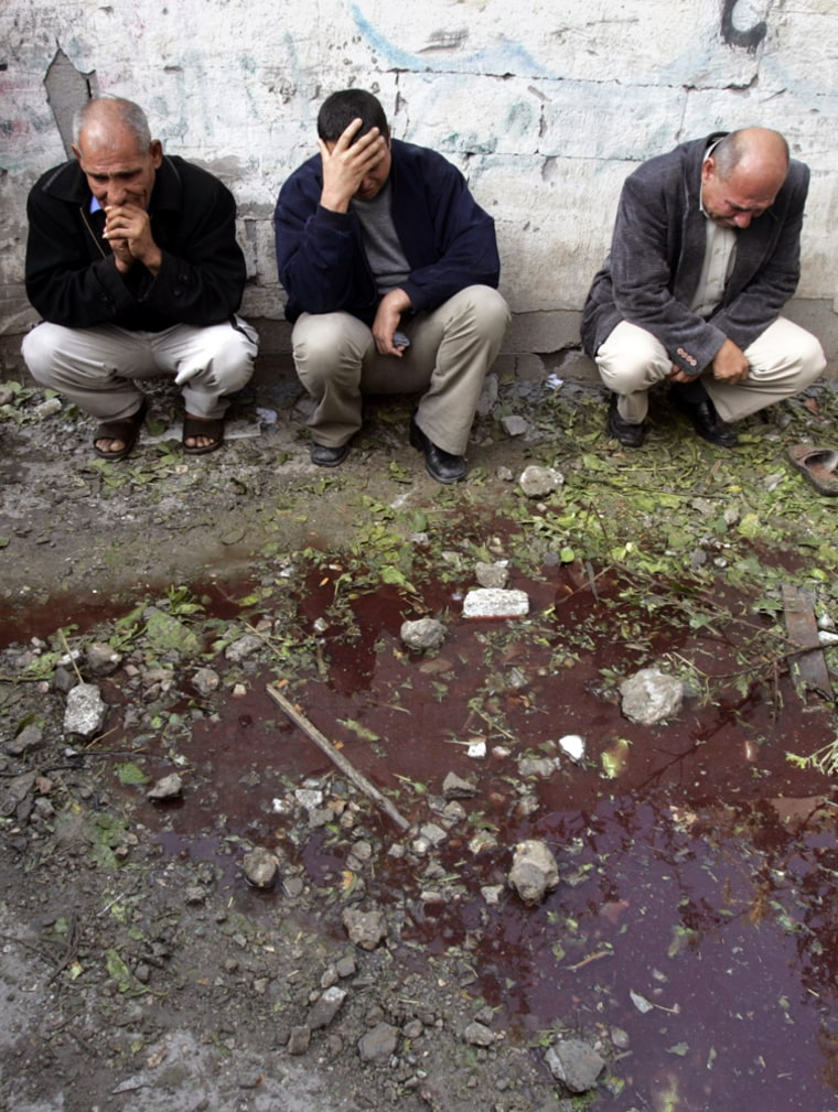 Palestinians sit next to a pool of blood mixed with water on a street in the northern Gaza Strip town of Beit Hanoun on Wednesday. Israeli tank shells landed in a residential neighborhood north of the town, killing at least 18 people in their sleep, including eight children, according to witnesses and hospital officials.