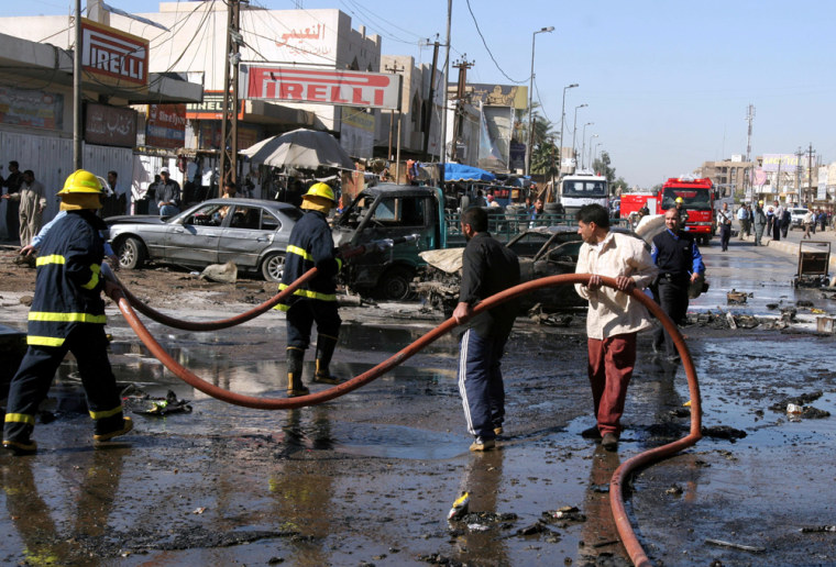 Iraqi firefighters remove debris followingone of the twosuicide bombings Thursday in Baghdad.