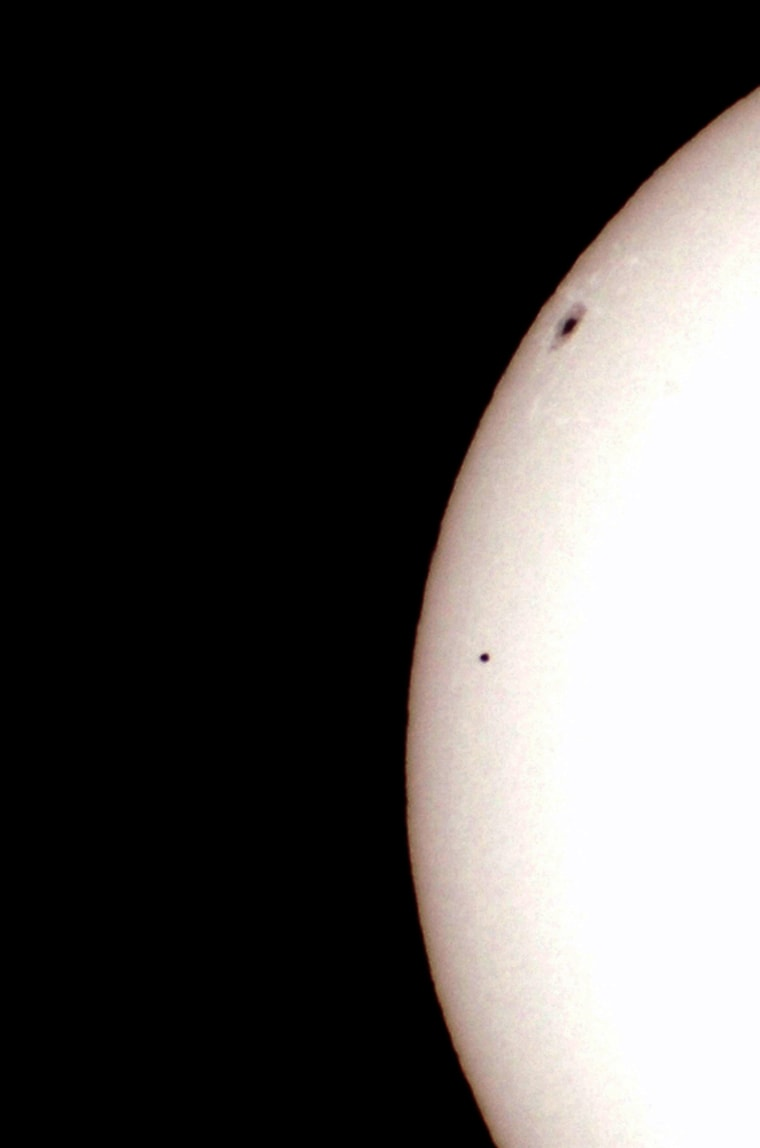 Planet Mercury passes in front of the Sun and below a large sunspot as seen through a solar filtered telescope from Palm Beach Gardens, Florida