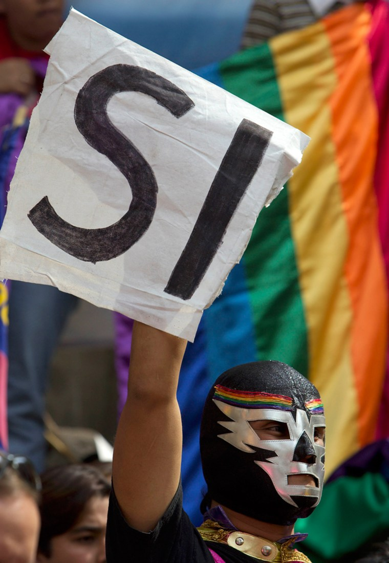"""A man dressed as a wrestler named Super Gay holds a sign that says """"Yes"""" during a Thursday rally on the steps of Mexico City's legislative house."""